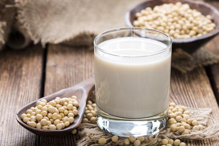 Vetro con latte di soia e semi su fondo in legno