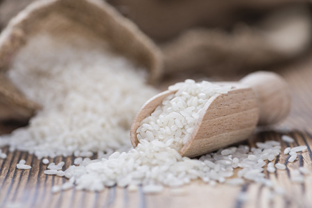 Portion of uncooked Rice on rustic wooden background Stock Photo