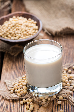 leche de soya: Leche de soja con algunas semillas (close-up shot) sobre fondo de madera Foto de archivo