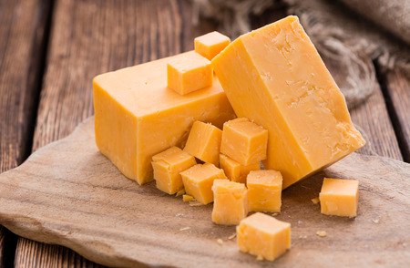 hard cheese: Portion of Cheddar (detailed close-up shot) on vintage wooden background Stock Photo