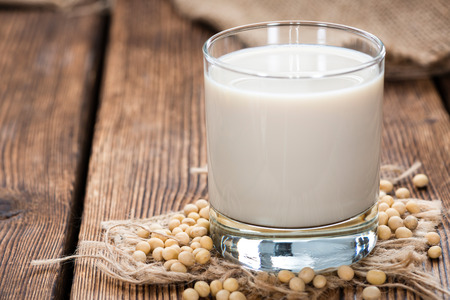 Soy Milk with some Seeds (close-up shot) on wooden background Stock Photo
