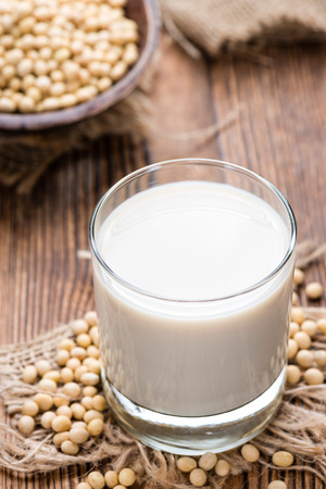 soymilk: Soy Milk with some Seeds (close-up shot) on wooden background Stock Photo