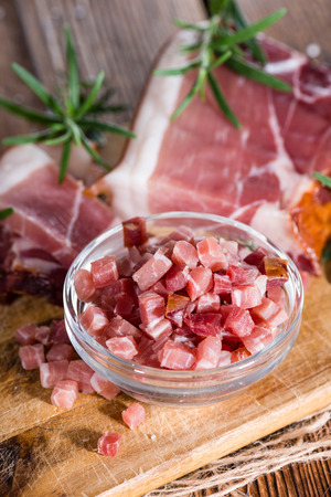 cubed: Diced Ham with Rosemary, Salt and pepper on wooden background