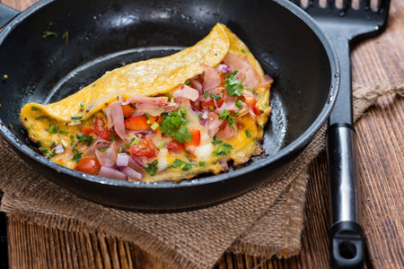 Frypan with Ham and Cheese Omelette on rustic wooden background