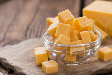 diced: Diced Cheddar (close-up shot) on rustic wooden background