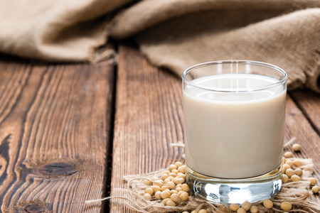 Soy Milk with some Seeds (close-up shot) on wooden background Banco de Imagens