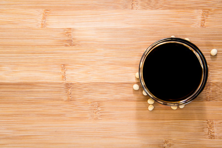 soja: Soy Sauce in a bowl (close-up shot) on bamboo background Stock Photo