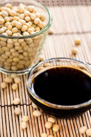 soja: Piccola ciotola con la salsa di soia su sfondo di bamb� Archivio Fotografico
