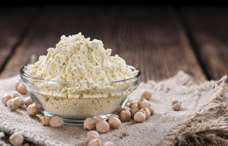 a portion: Portion of Chick Pea flour on vintage wooden background Stock Photo