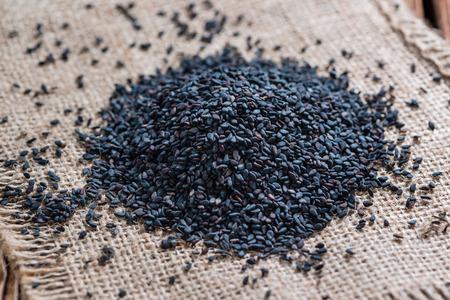 black sesame: Small portion of black Sesame (close-up shot) on wooden background Stock Photo