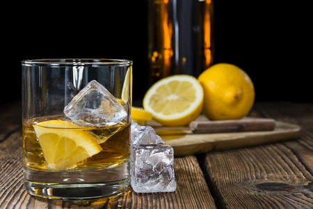Whiskey with lemon and ice cubes on rustic wooden background