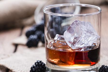 liqueur: Blackberry Liqueur (as shot) on wooden background Stock Photo