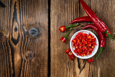 Cutted red Chilis in a bowl (close-up shot) on wooden background Banco de Imagens