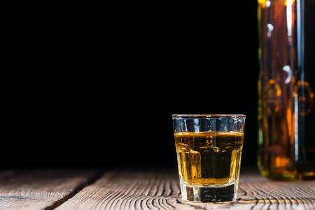 木製の背景上のウイスキー (クローズ アップ ショット) とガラスをショットします。