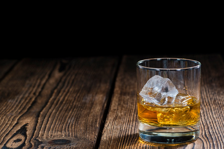 Glass with Whiskey (close-up shot) on rustic wooden background