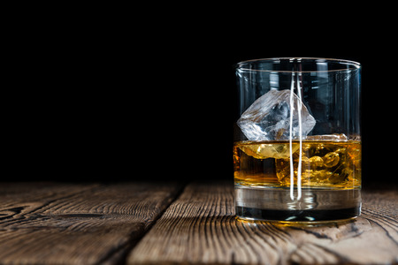 brandy: Single Malt Whiskey with Ice Cubes on wooden background