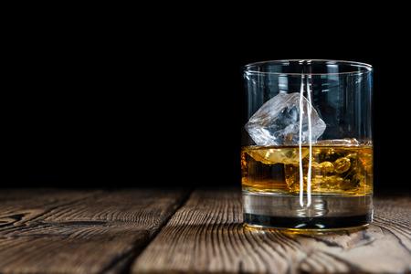 tomando alcohol: Whisky de malta con cubos de hielo sobre fondo de madera