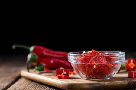 mexican food: Cutted red Chilis in a bowl (close-up shot) on wooden background Stock Photo