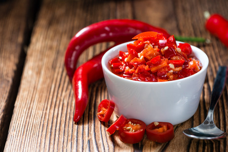 chili: Preserved red Chilis (close-up shot) on wooden background