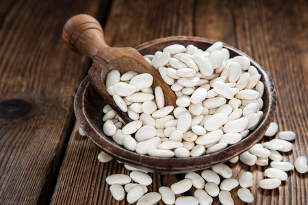 Heap of White Beans (close-up shot) on an old wooden table)