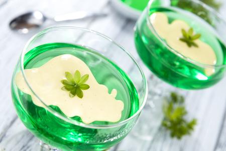 gelatine: Woodruff Jelly with Vanilla Sauce (on wooden background)