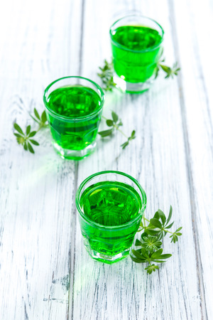 sweet woodruff: Woodruff Liqueur in small shot glasses (on wooden background)
