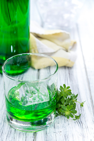 woodruff: Woodruff Liqueur in a small shot glass (on wooden background)