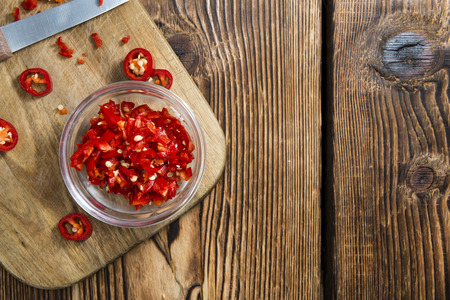 cutted: Red Chilis (cutted) on vintage wooden background