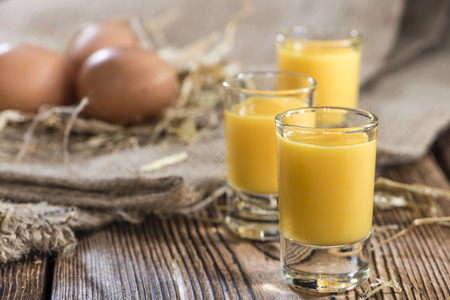 fresh cream: Homemade Egg Liqueur on dark vintage wooden background Stock Photo