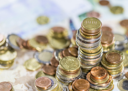 schein: Stacked Euro Coins on Banknotes as detailed close-up shot