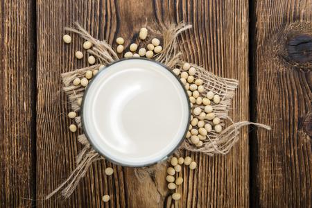 leche de soya: Vidrio con leche de soja y semillas en el fondo de madera