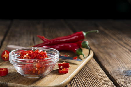 cutted: Cutted red Chilis (close-up shot) on wooden background