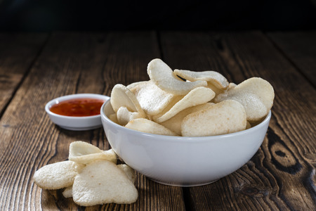 keropok: Prawn Crackers (Krupuk) on wooden background (close-up shot)