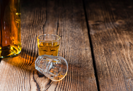 Shot glass with Whiskey (close-up shot) on wooden background photo