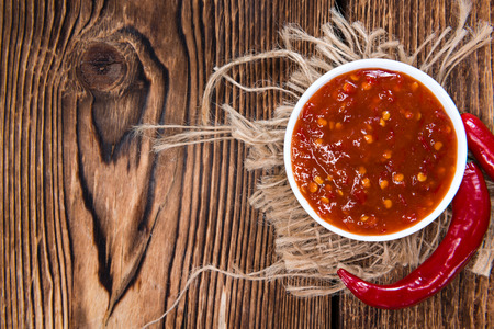 thai chili pepper: Portion of Chili Sauce (Sambal Oelek) on rustic wood Stock Photo