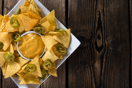 nachos: Nachos with Cheese Sauce (close-up shot) on wooden background