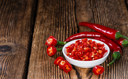 Cutted red Chilis in a bowl (close-up shot) on wooden background photo