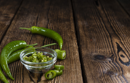 cutted: Green Chilis (cutted) on an old rustic wooden table