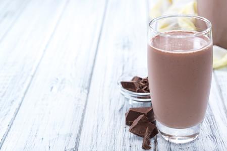 冷たいチョコレート牛乳を飲む (接写) 木製の背景に