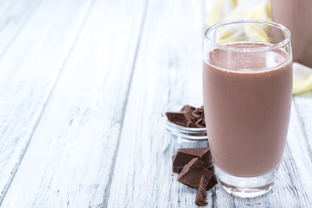 protein: Cold Chocolate Milk drink (close-up shot) on wooden background