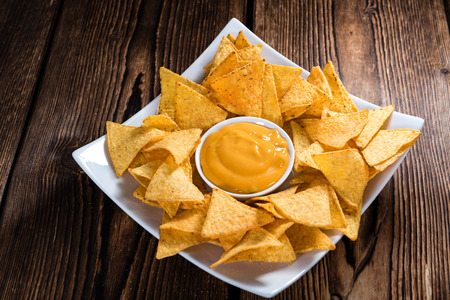 nacho: Portion of Nachos (with Cheese Dip) on an old wooden table