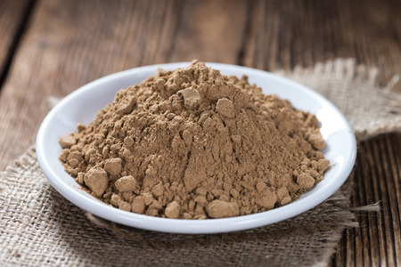 energizing: Portion of Guarana Powder on dark wooden background