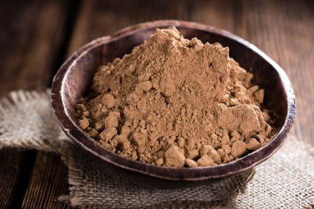 Heap of Guarana Powder (close-up shot) on wooden background