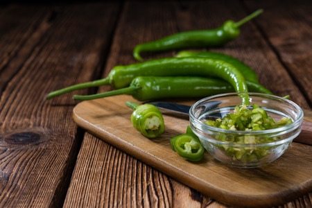 cutted: Cutted green Chilis (close-up shot) on rustic wooden background