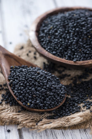 black seeds: Heap of Black Lentils on wooden background (close-up shot) Stock Photo