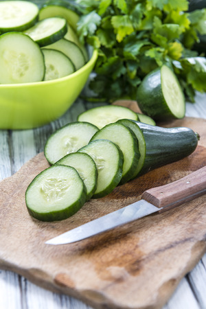 Sliced Cucumbers (close-up shot) on an old wooden table
