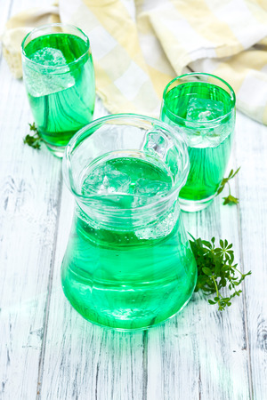 woodruff: Sparkling Woodruff Drink in a glass (on bright wooden background) Stock Photo