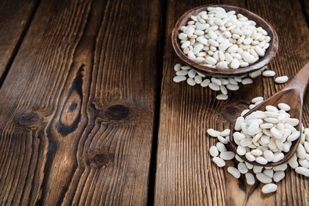white beans: Some White Beans on a rustic wooden background (close-up shot)
