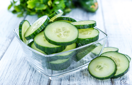 cucumber: Heap of fresh sliced Cucumbers on an old wooden table