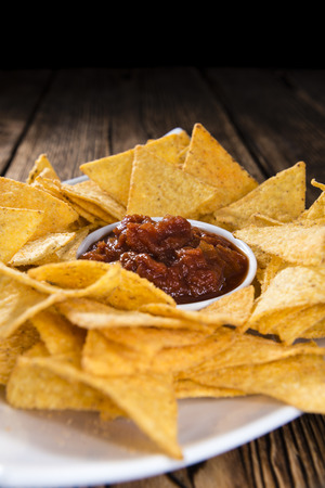 mexican food: Portion of Nachos (with Salsa Dip) on an old wooden table